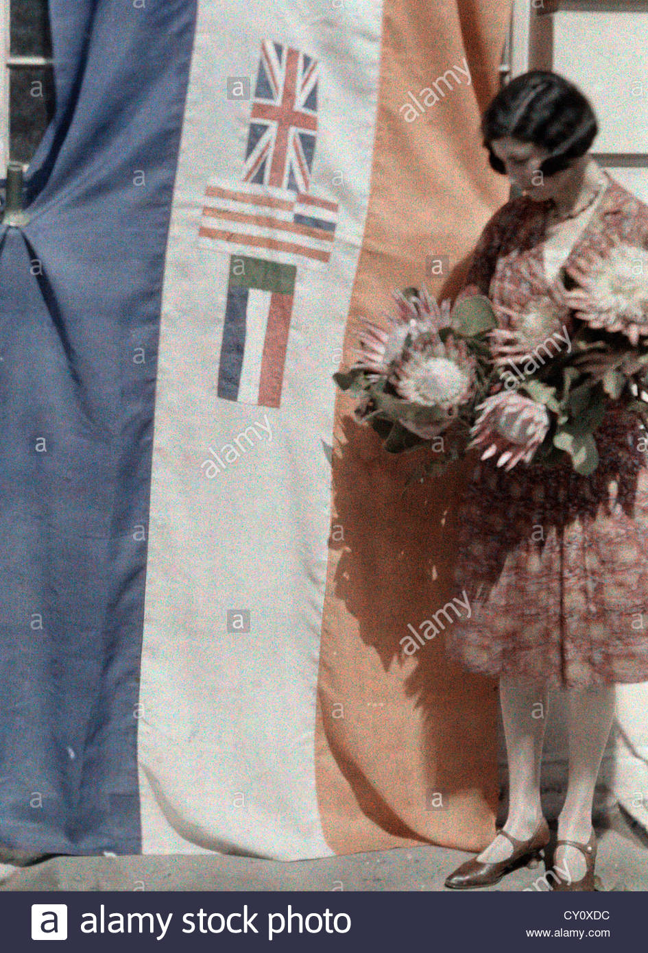 Miss Cape Town stands with the Union banner and national flowers. - Stock Image