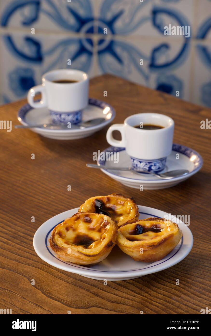 Pasteis de Nata or Pasteis de Belem; custard tarts, on a café table with bica coffees; Belém, Lisbon, - Stock Image
