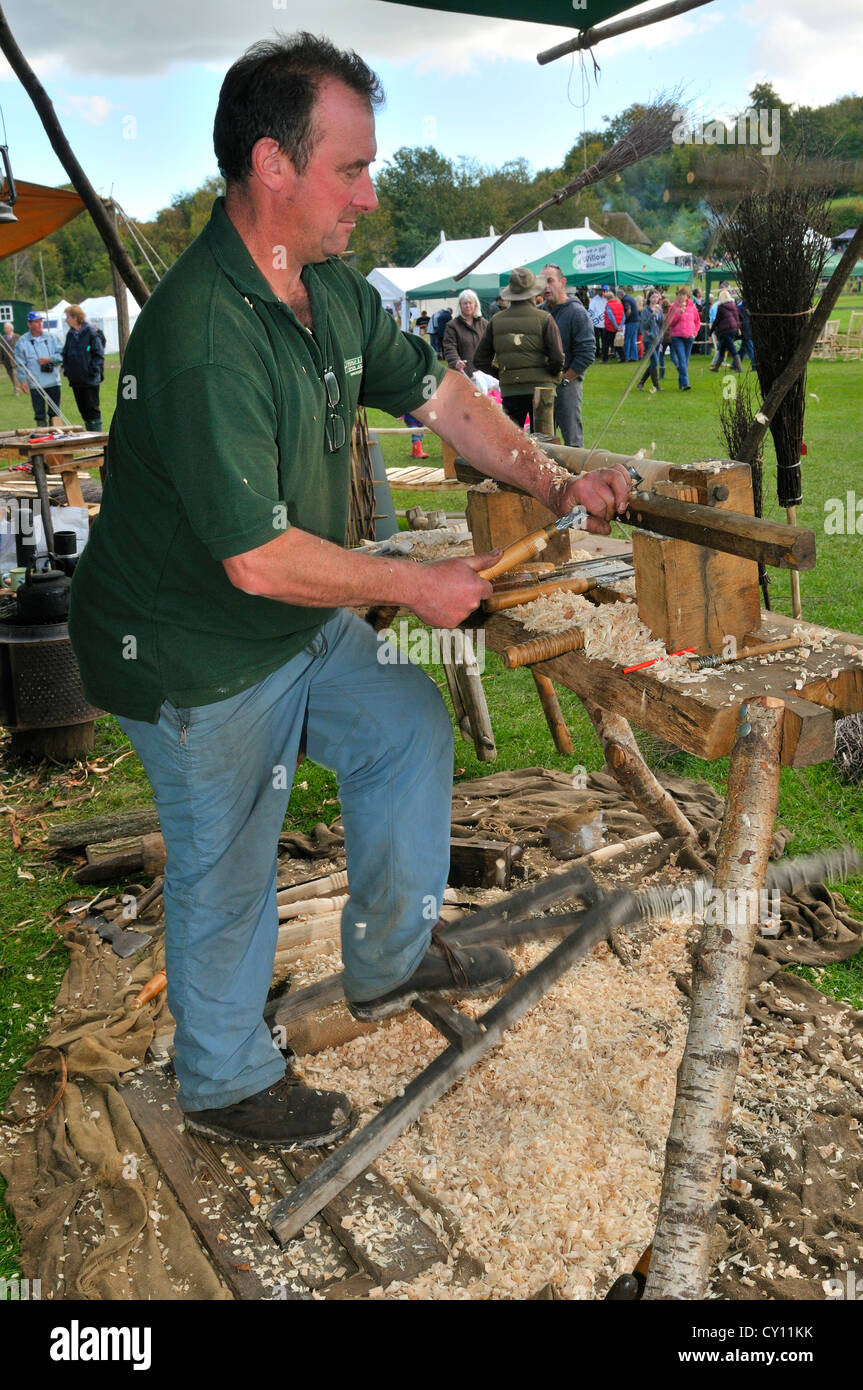Man demonstrating  Pole Lathe Turning on a treadle lathe ,making brush handles at the Autumn Countryside Show - Stock Image