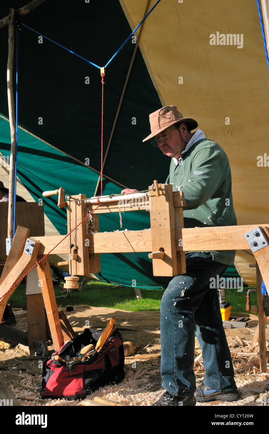 Man demonstrating Pole Lathe Turning , on a treadle lathe,  making chair spindles at the Autumn Countryside Show - Stock Image