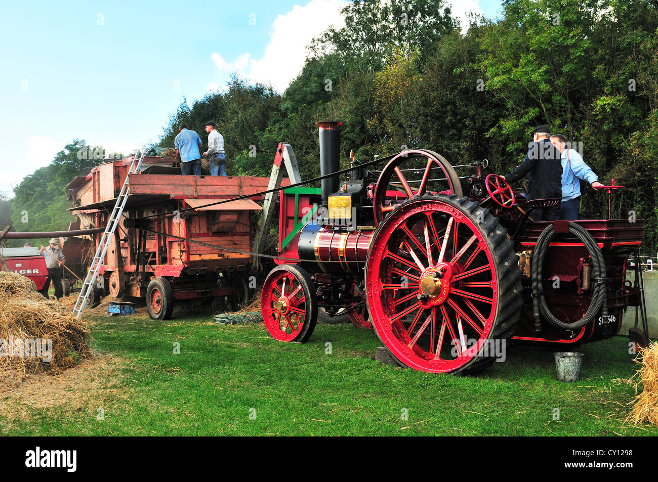 Foden Steam engine and  Marshall Sons & Co. Ltd. Threshing drum process in action, threshing out the grain from - Stock Image