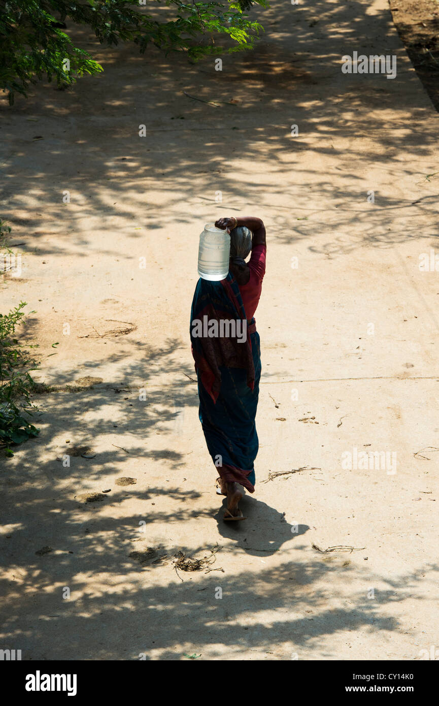 Rural Indian village woman collecting water from a communal water tank. Andhra Pradesh, India - Stock Image