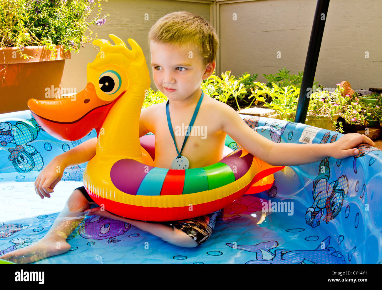 A five-year-old boy with autism sits in a wading pool, protected by a duck floaty. - Stock Image