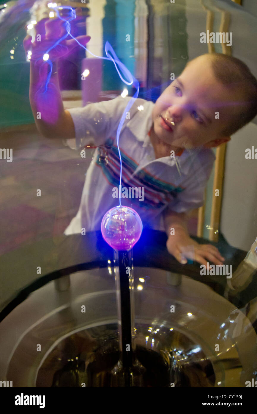A young boy with autism discovers a new visual input through interaction with a plasma ball. - Stock Image