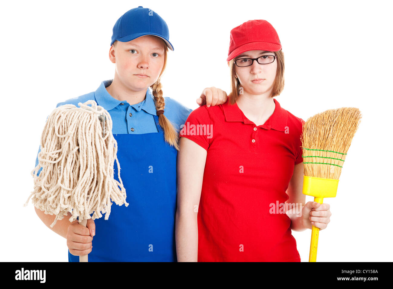 Two serious looking teenage girls, dressed in uniforms for menial jobs and holding a broom and mop. Isolated on - Stock Image