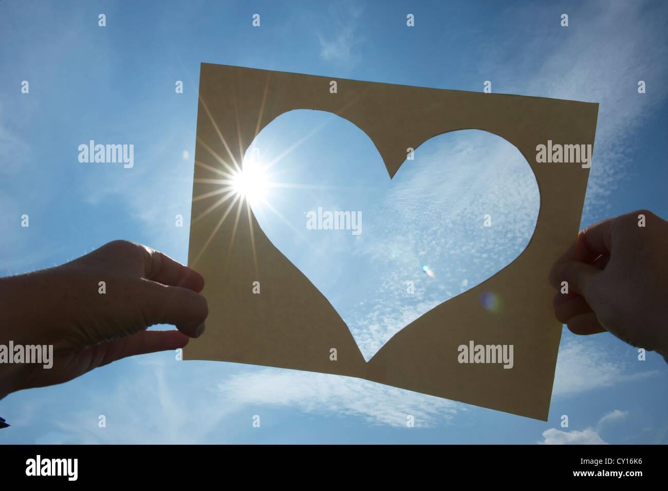 ein Herz aus Pappe in den Himmel gehalten gegen die Sonne, a heart cut of a piece of paper, two hands holding it - Stock Image