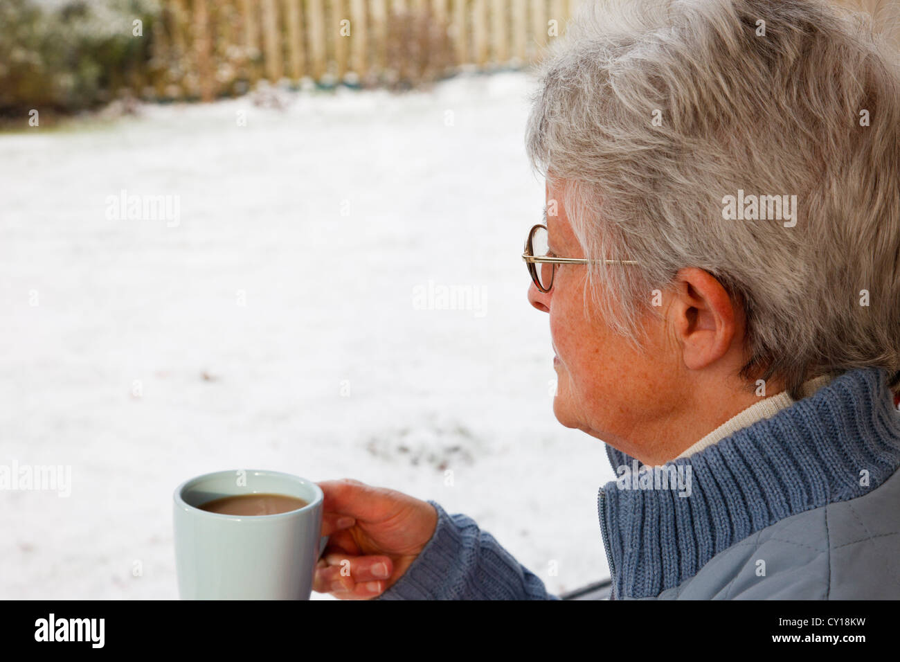 Lonely senior woman holding a hot drink and looking out through a window to snow in the garden outside in winter. - Stock Image