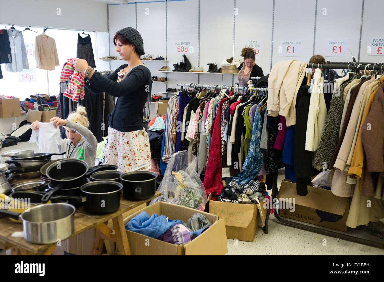 Women browsing racks of second hand clothes and goods on sale in a ...