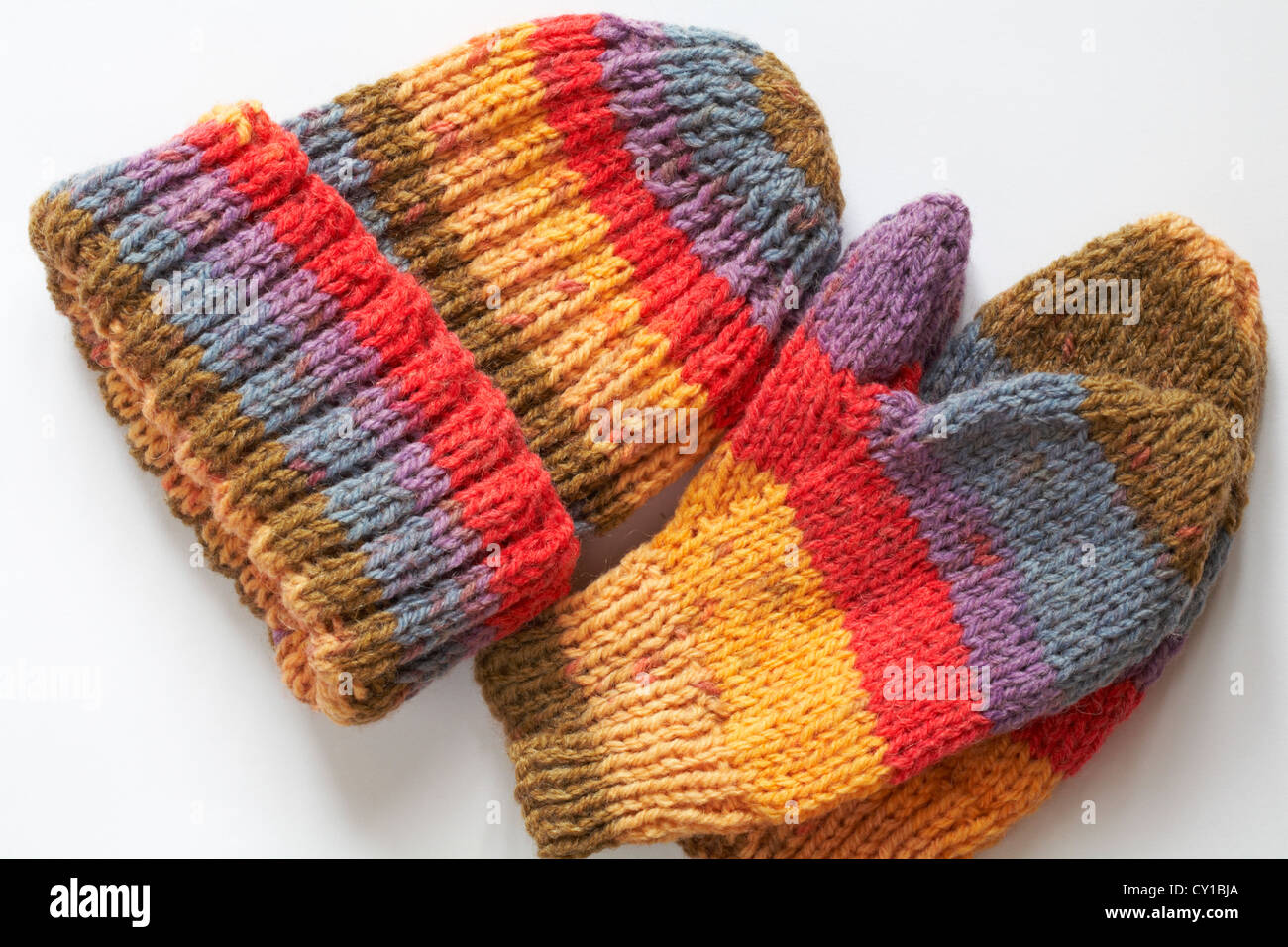 Brightly coloured knitted hat and mitts isolated on white background Stock Photo