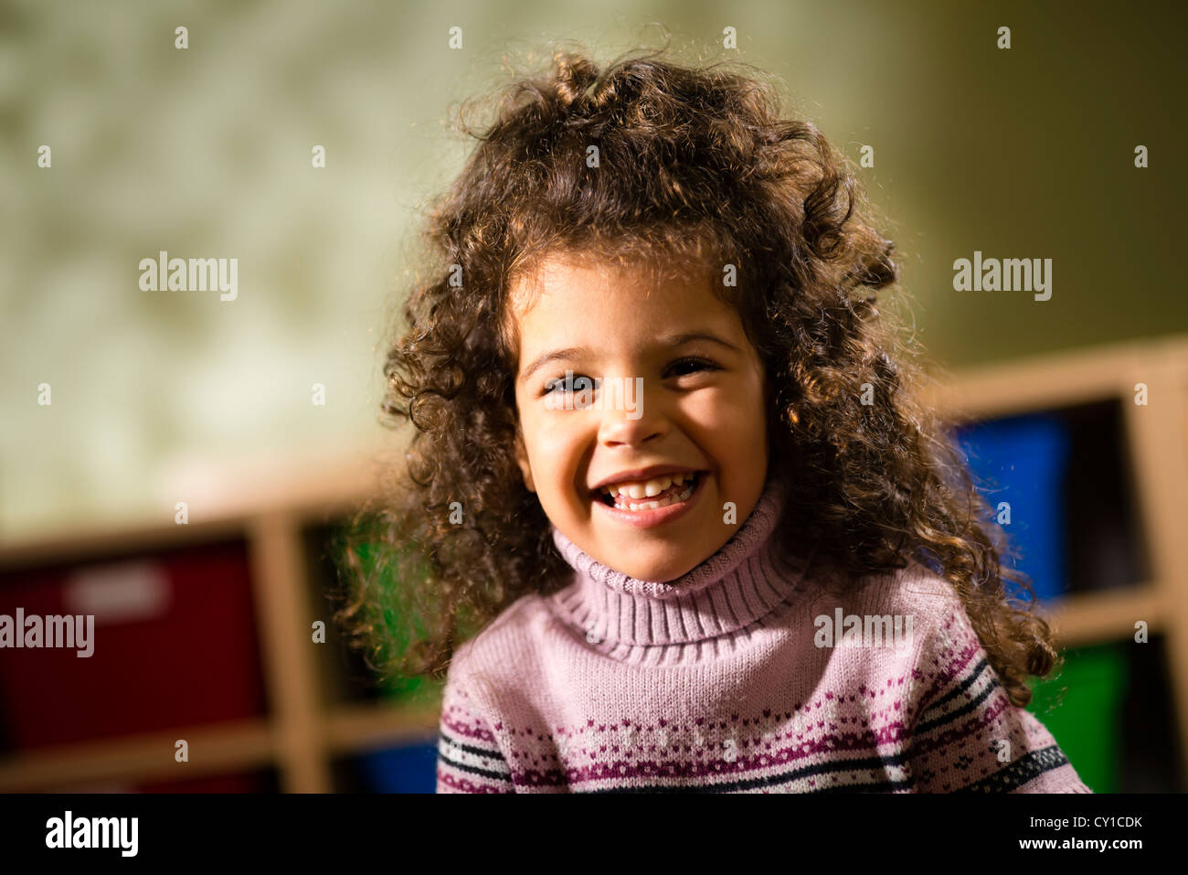 Portraits of children, happy 3 years old female with curly hair smiling and looking at camera in kindergarten - Stock Image