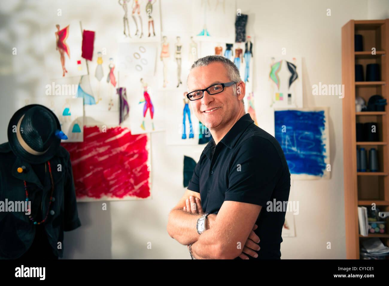 Confident entrepreneur, portrait of happy mature man working as fashion designer and dressmaker in atelier - Stock Image
