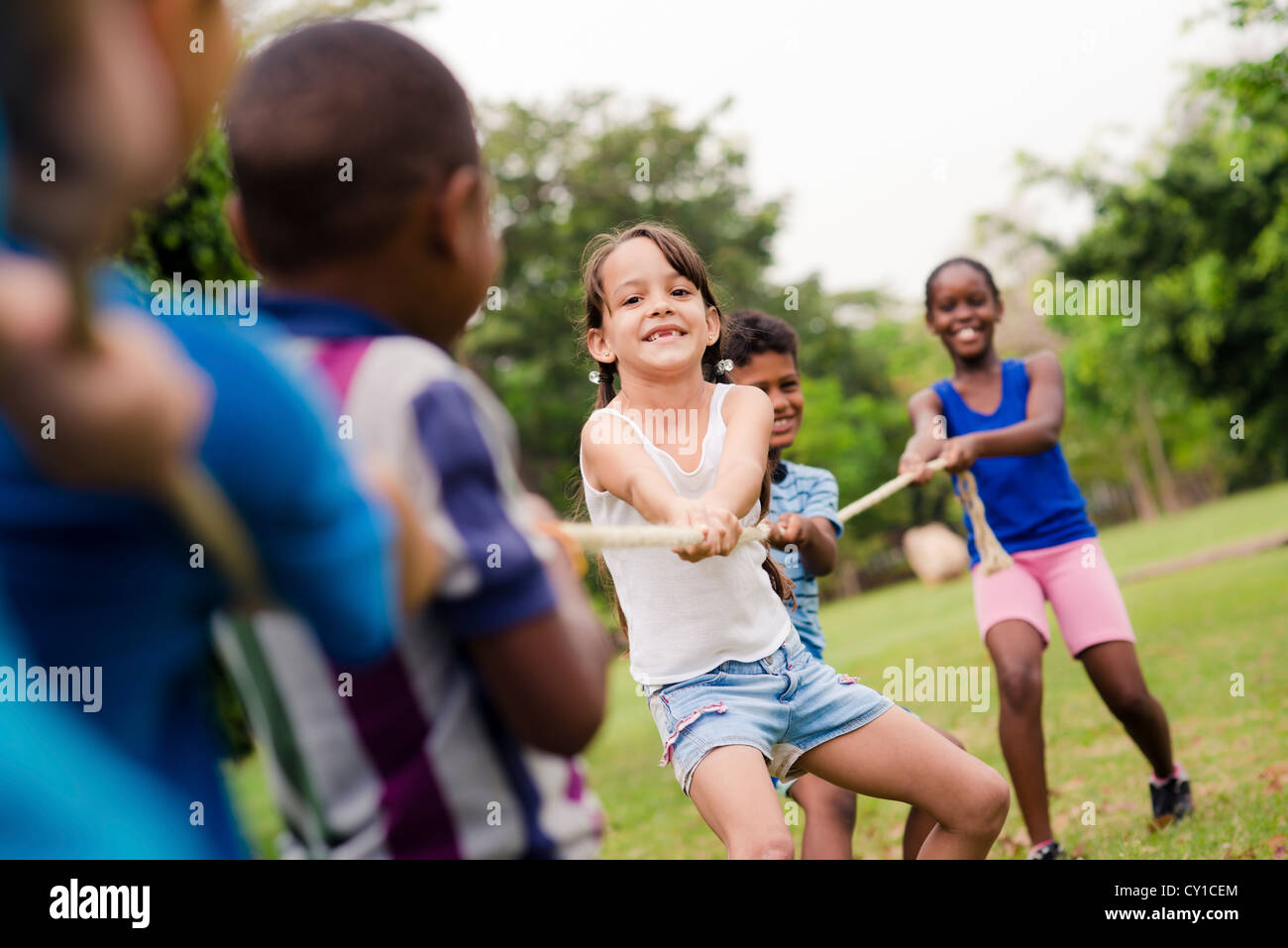 Children and recreation, group of happy multiethnic school kids playing tug-of-war with rope in city park. Summer - Stock Image
