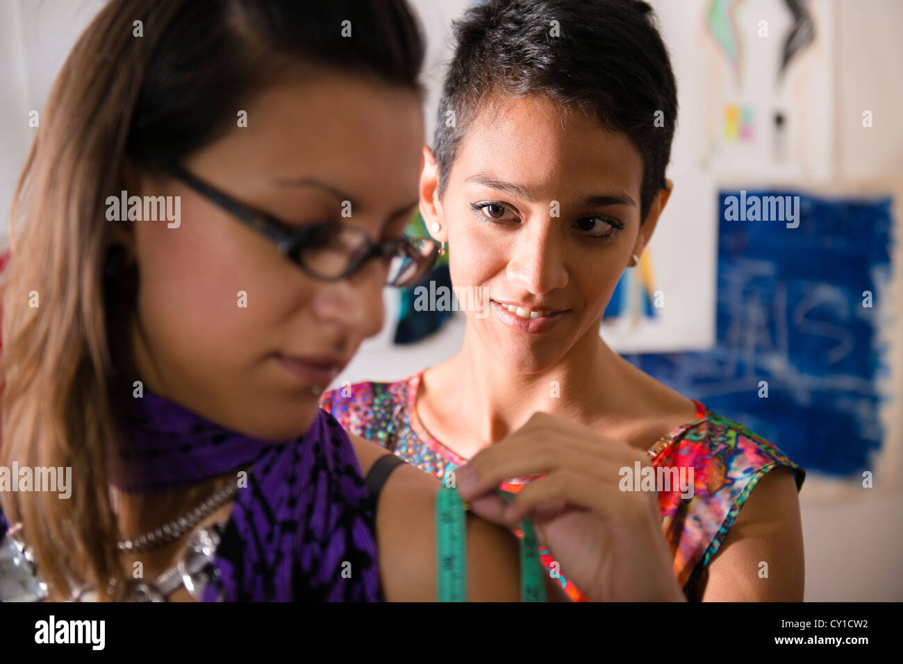 Fashion industry and young women, tailor and female customer in atelier for new dress - Stock Image