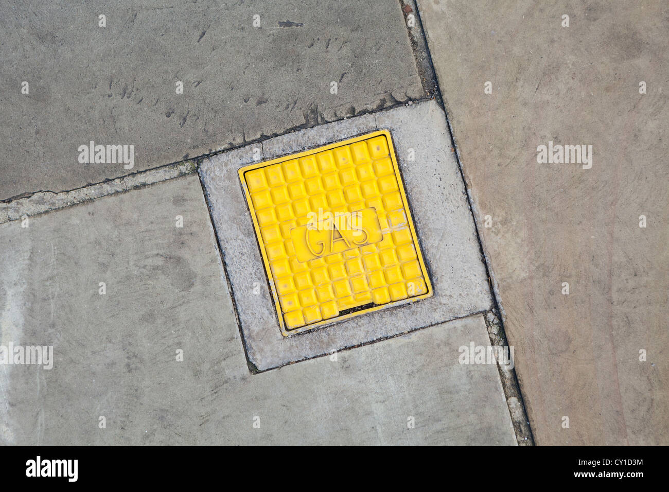 Gas manhole cover in pavement, UK - Stock Image