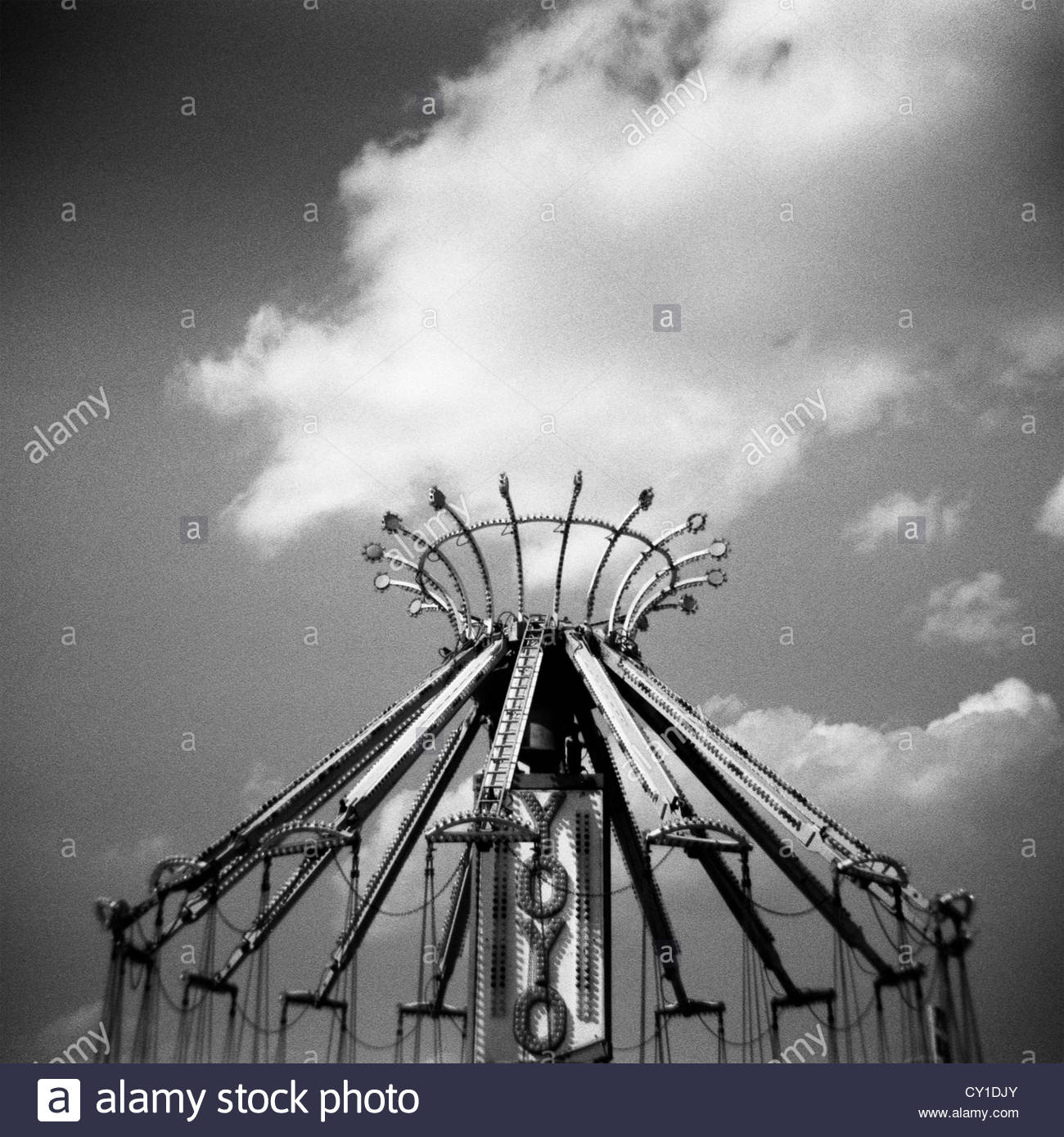 Monochrome Holga carnival image of Yoyo ride with clouds - Stock Image