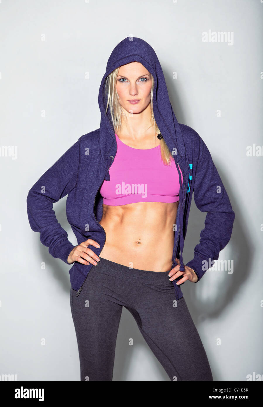Confident woman in sportswear posing for camera against white background. Stock Photo