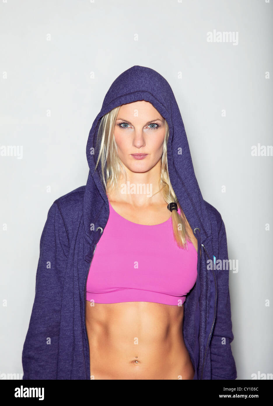 Confident woman in sportswear posing for camera against white background. - Stock Image