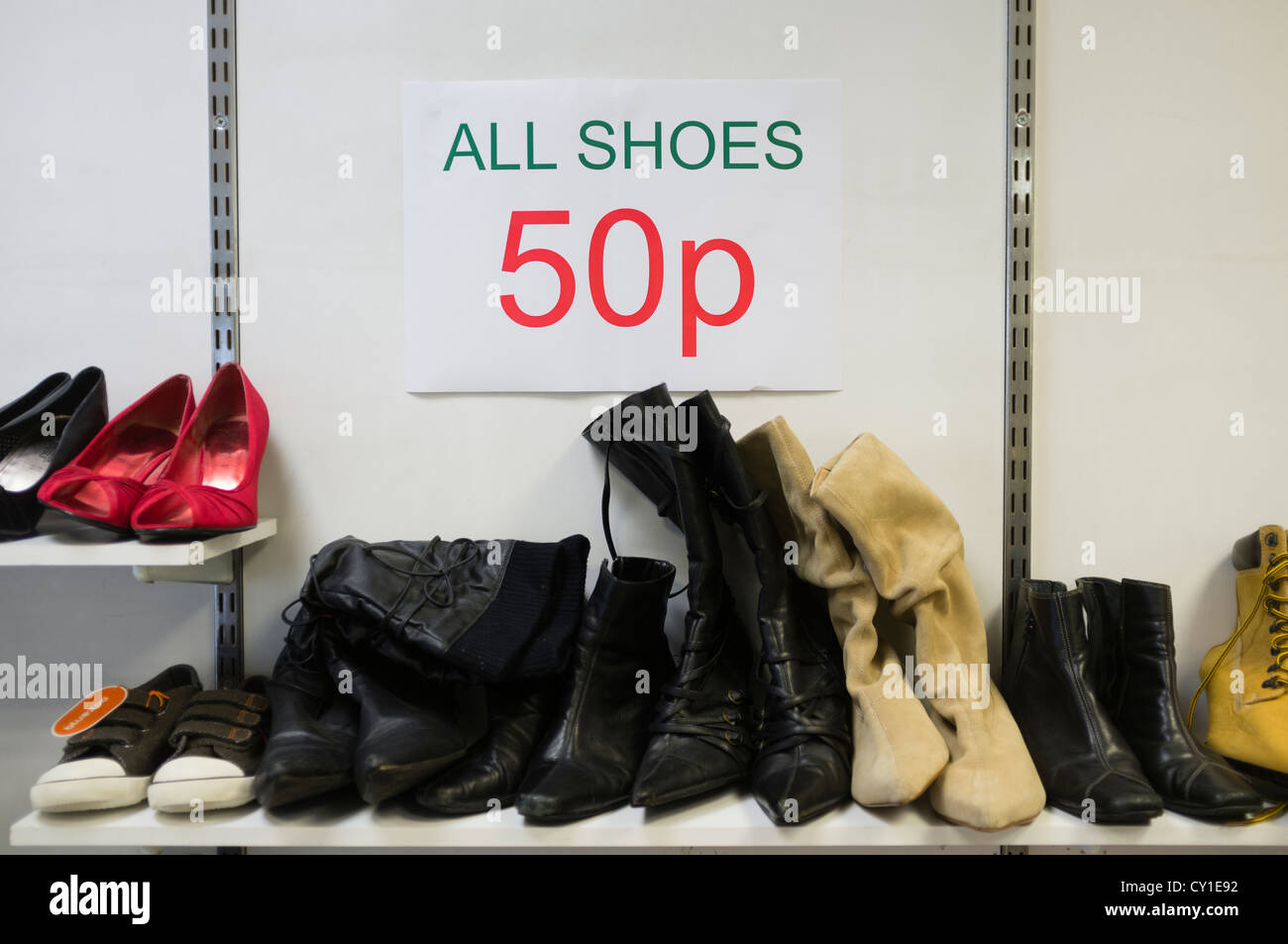 Pairs of old second hand used cheap bargain shoes on sale for 50p in a discount charity store shop uk - Stock Image