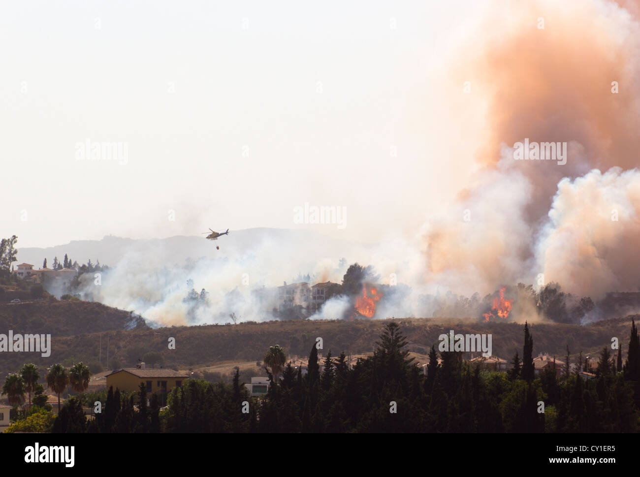 Rescue helicopter helping to extinguish wildfire. Mijas Costa, Malaga, Costa del Sol, Andalucia, Spain. - Stock Image