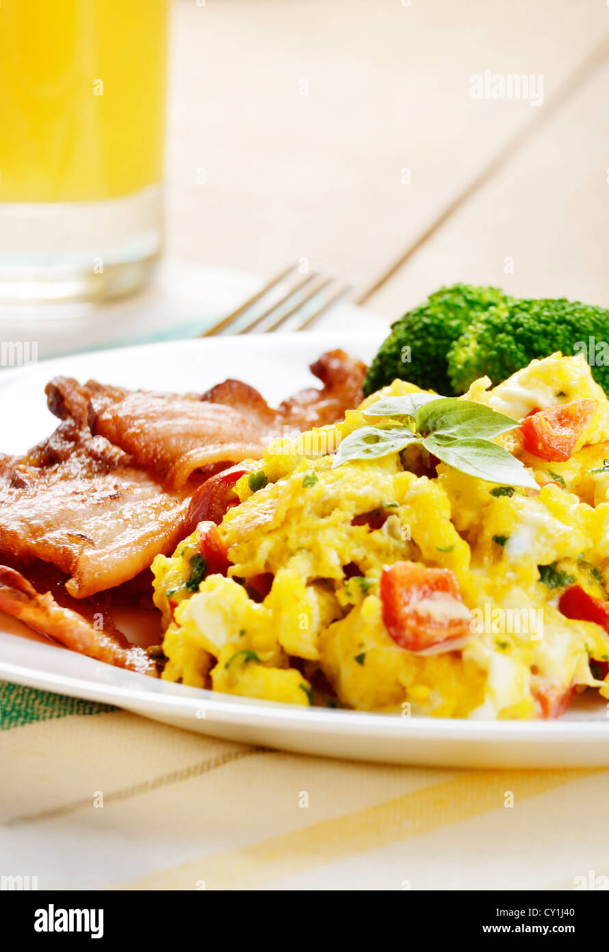 Omelet with vegetables, fried bacon and orange juice - Stock Image