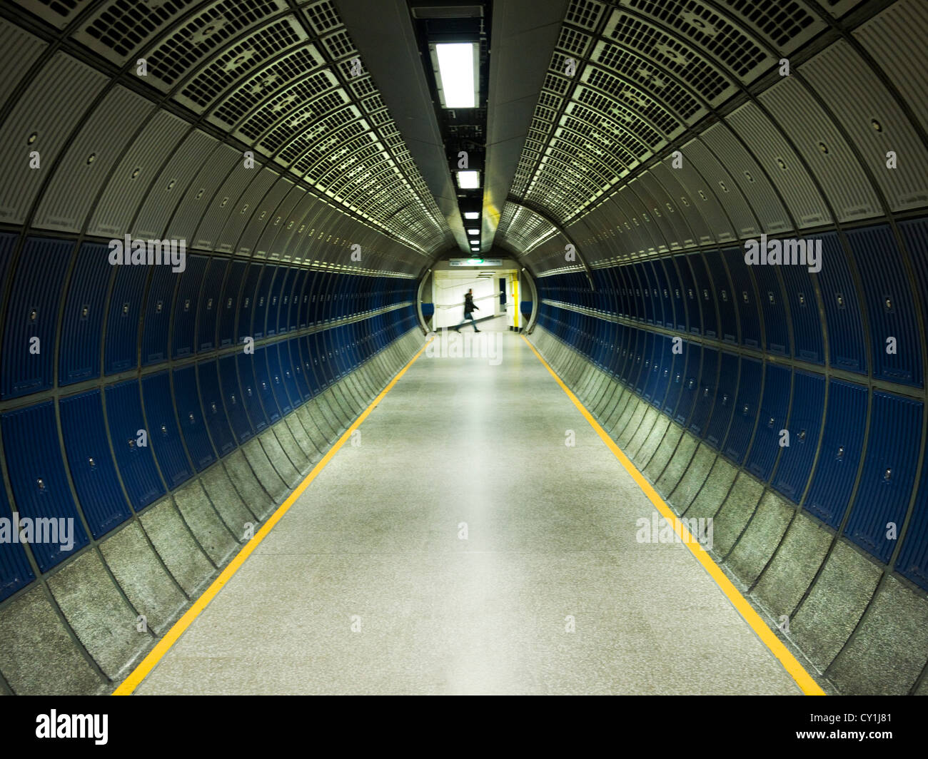 Modern Underground tunnel with lone figure walking across in distance - Stock Image