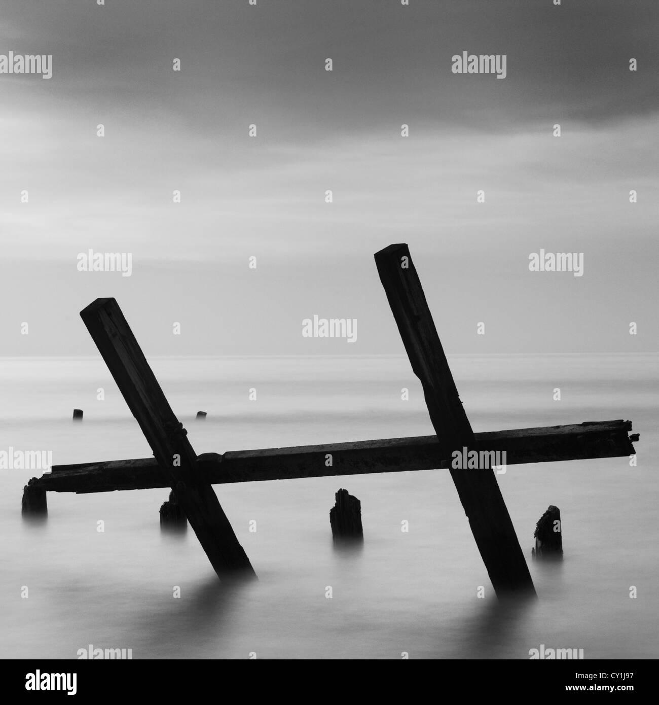 Broken wooden groynes in the sea at Happisburgh, Norfolk, England - Stock Image