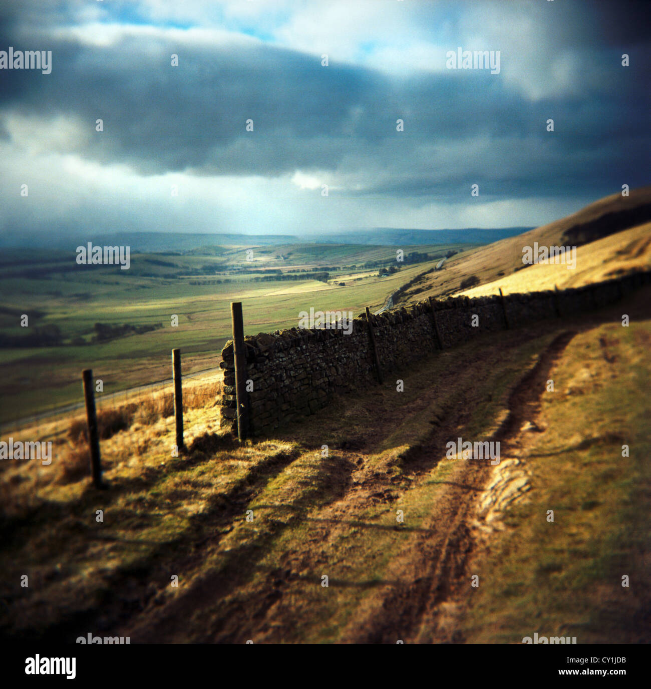 Moorland view with farm track looking down across fields with stormy skies at Rushup Edge, Peak District, England - Stock Image