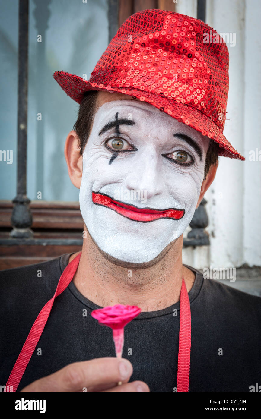 A portrait of a clown street performer in Las Palmas Gran Canaria Spain wearing a red hat with white face, holding Stock Photo