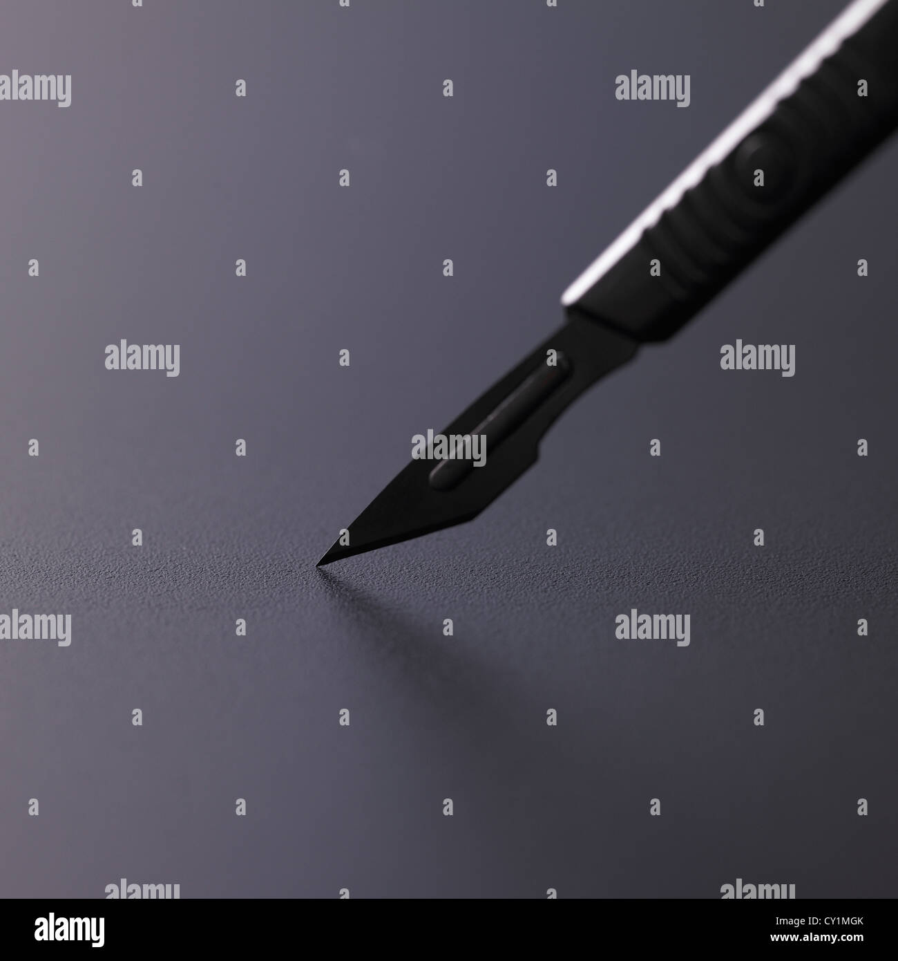 Surgical scalpel closeup with blade tip touching grey metallic worktop, differential focus - Stock Image