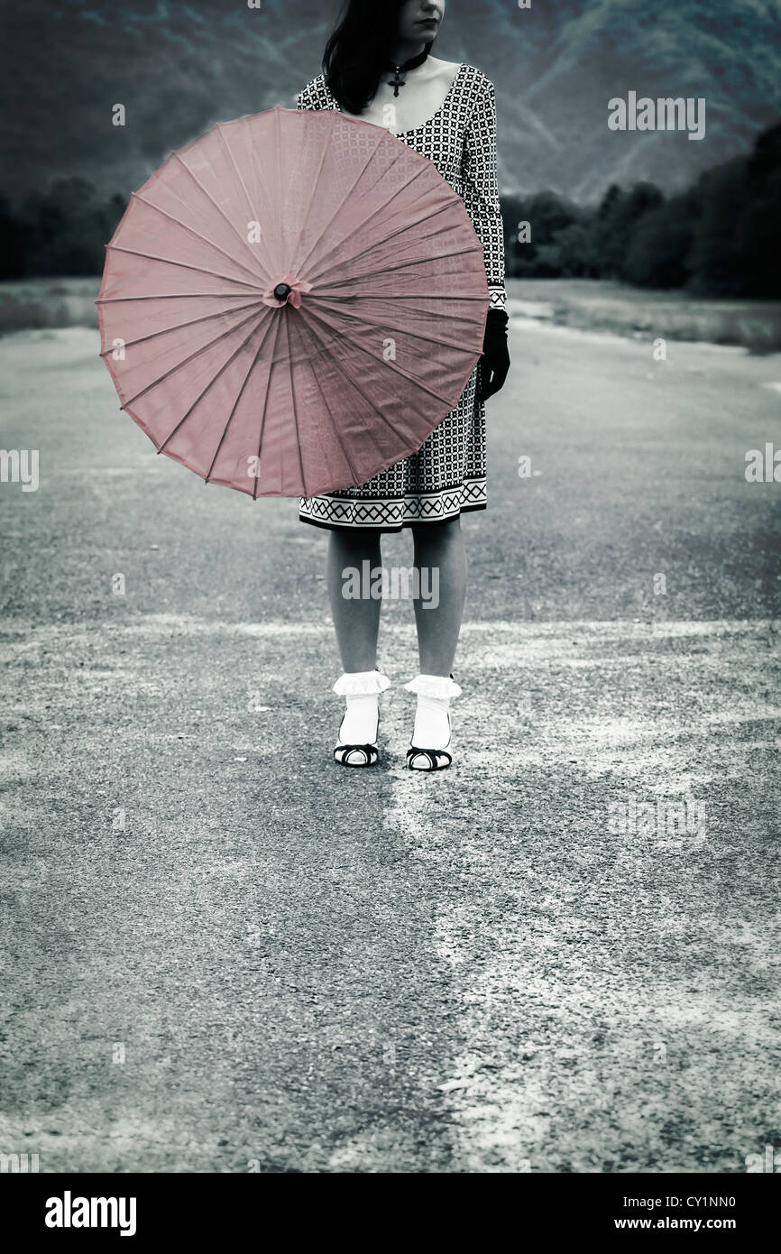 a woman in a black and white dress with a red umbrella - Stock Image