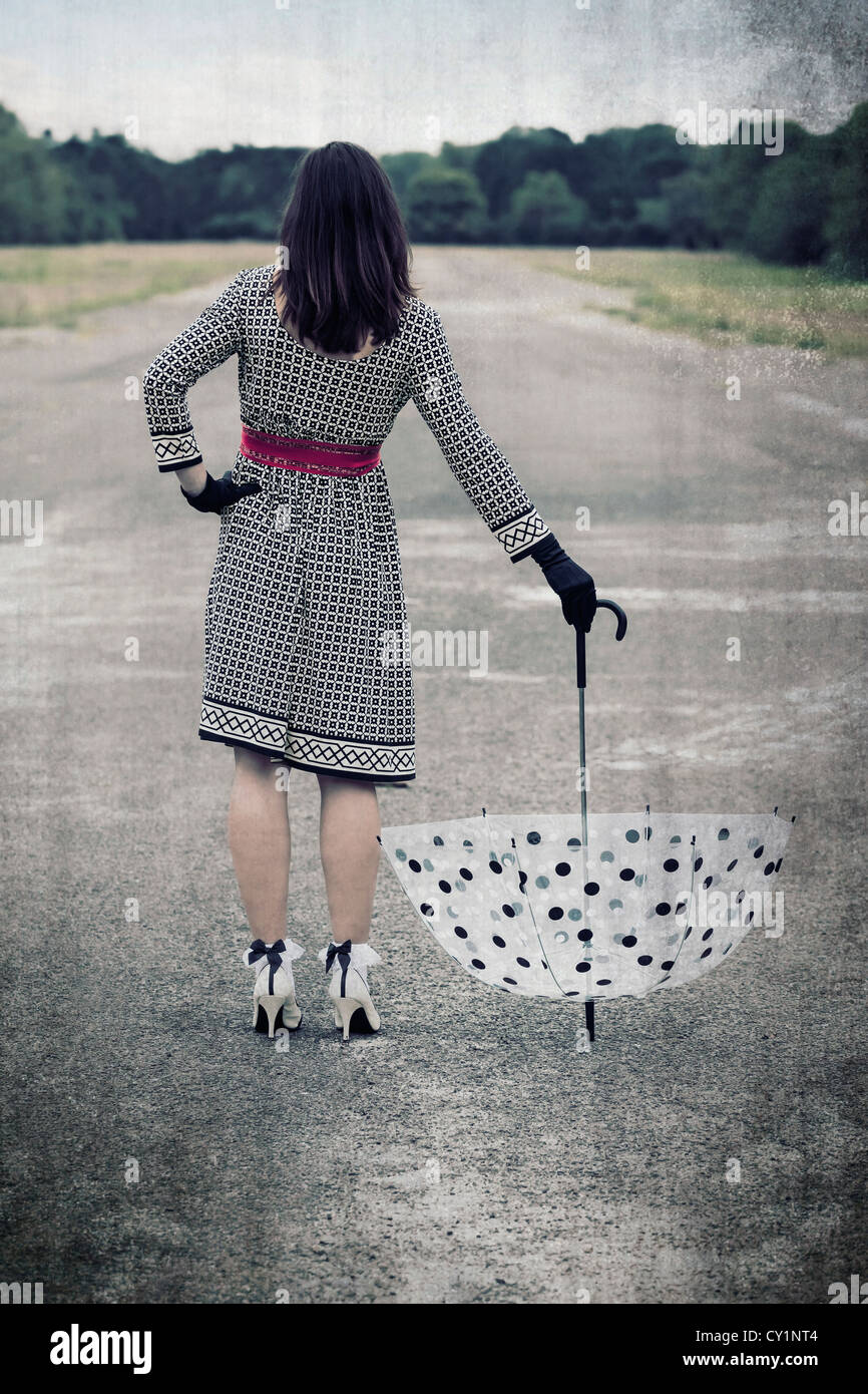 a woman is standing on a street and holding a vintage umbrella Stock Photo