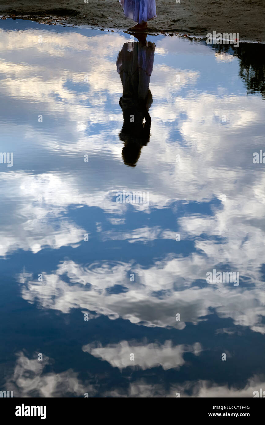 reflection of a woman in a white dress in a pond Stock Photo