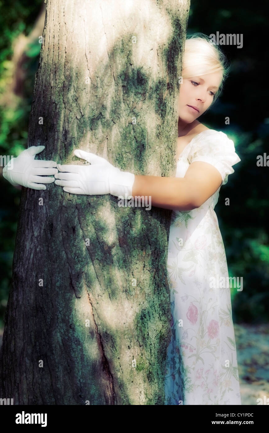 a woman in a floral dress is hugging a tree - Stock Image