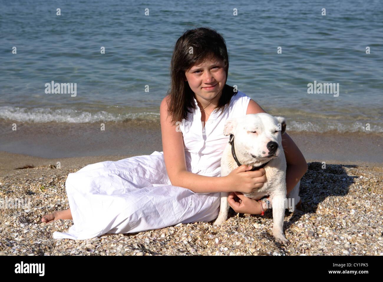 girl teenager dog sea holiday Staffordshire Bull Terrier - Stock Image