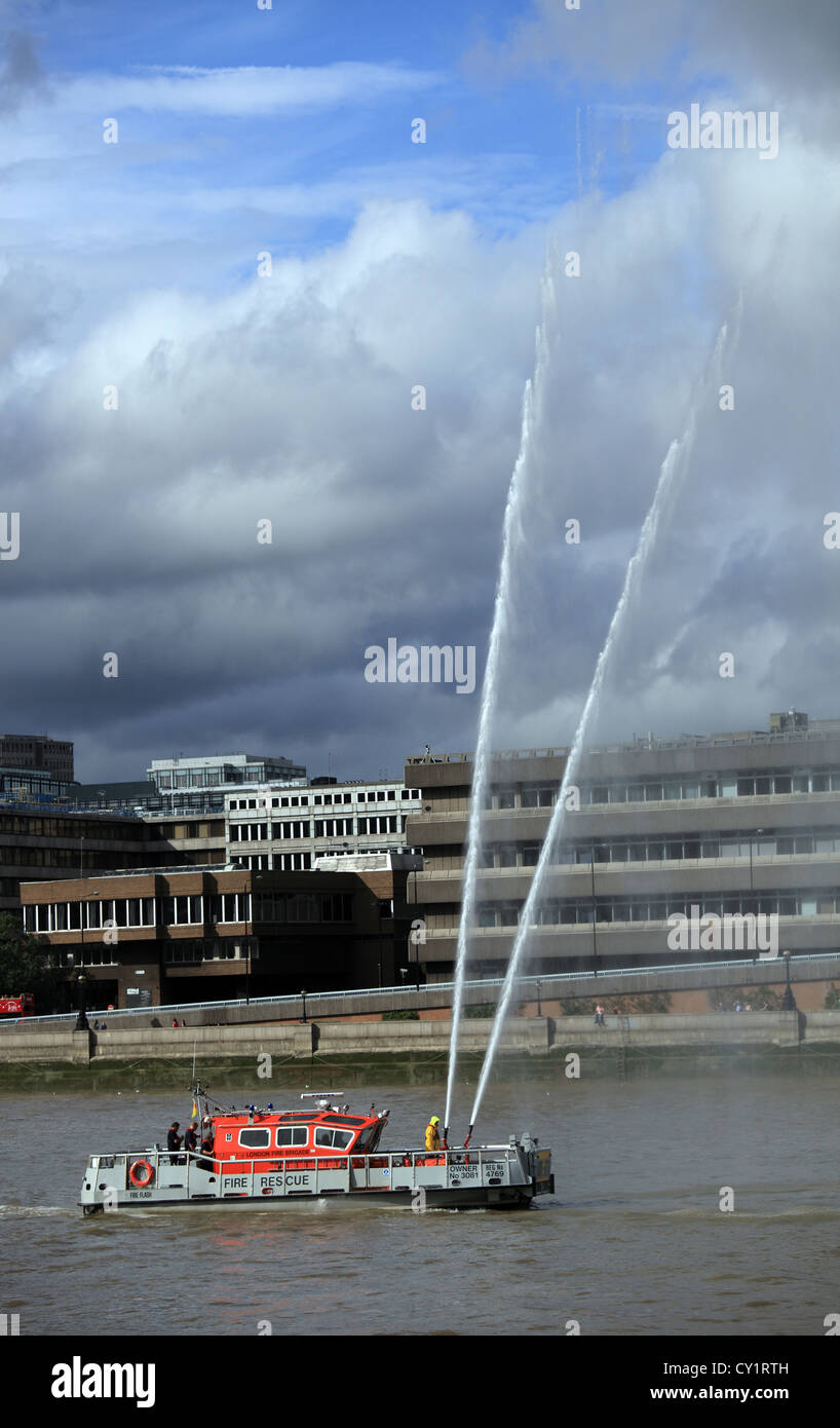 London Fire Brigade Fire and Rescue service river section operating fire hoses during the Thames Festival 2011 - Stock Image