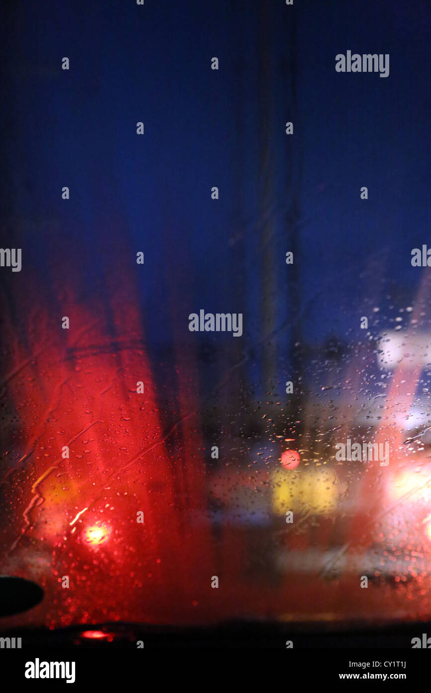 Lorry's Tail Lights At Night Through Car Windscreen In The Rain On Motorway England - Stock Image