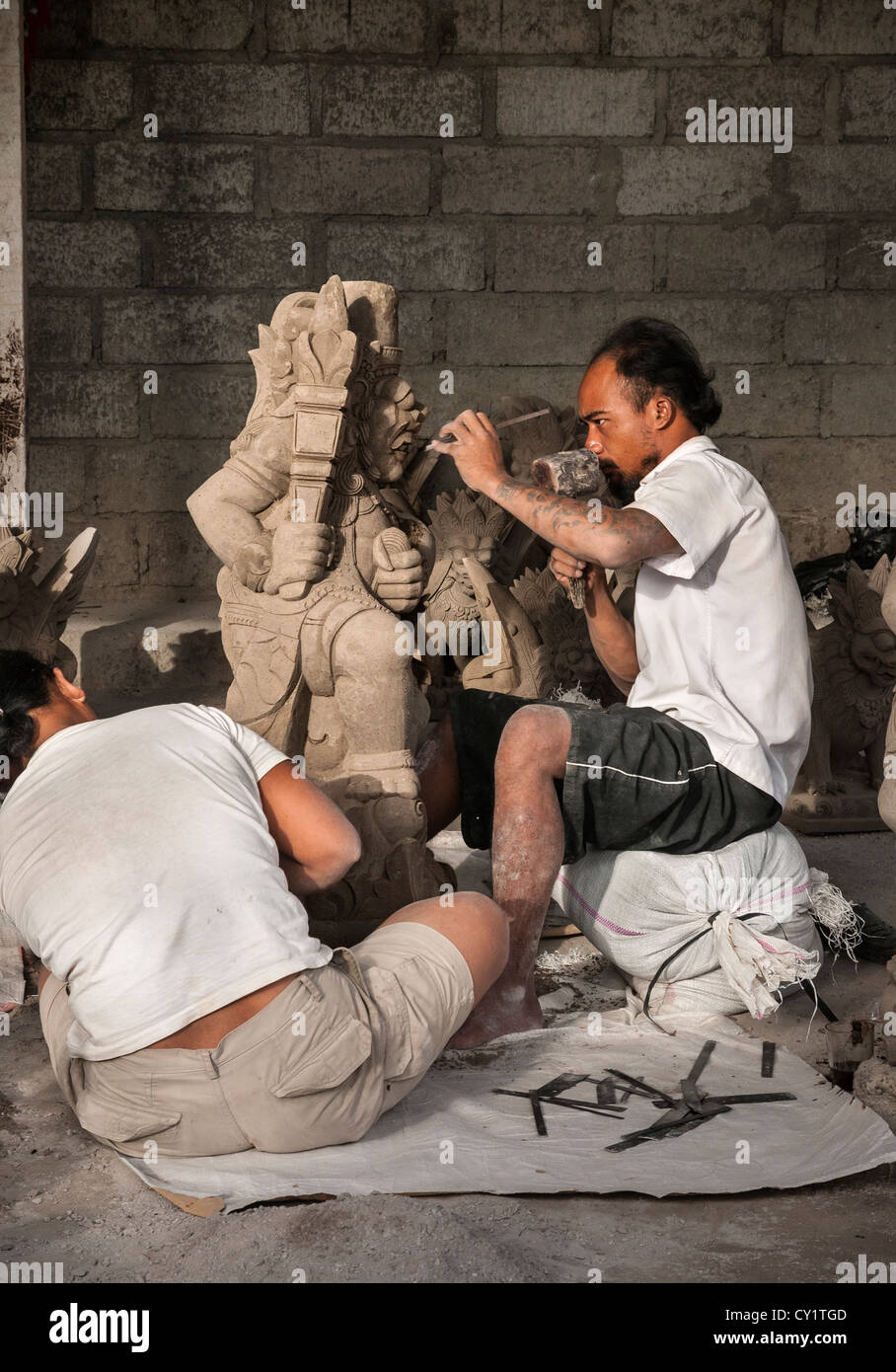 Stone mason carving a religious statue. Near Ubud, central Bali, Indonesia - Stock Image
