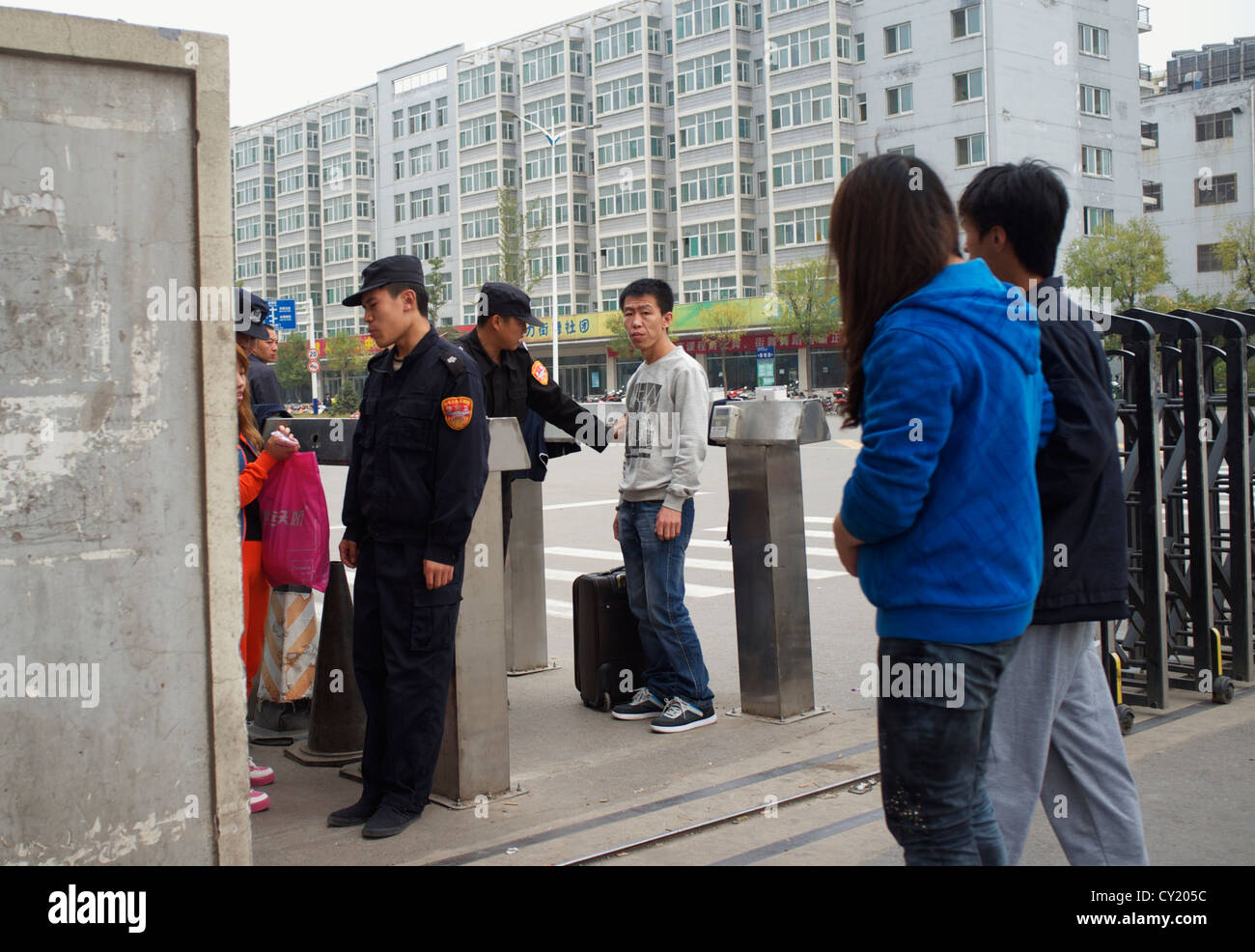 Security guards block a worker who forgot to carry his access card at no.3 gate of Foxconn Taiyuan factory, Shanxi, - Stock Image