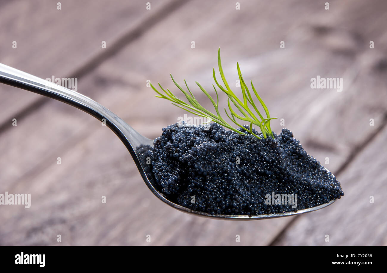 Caviar and Dill on a Spoon against wooden background - Stock Image