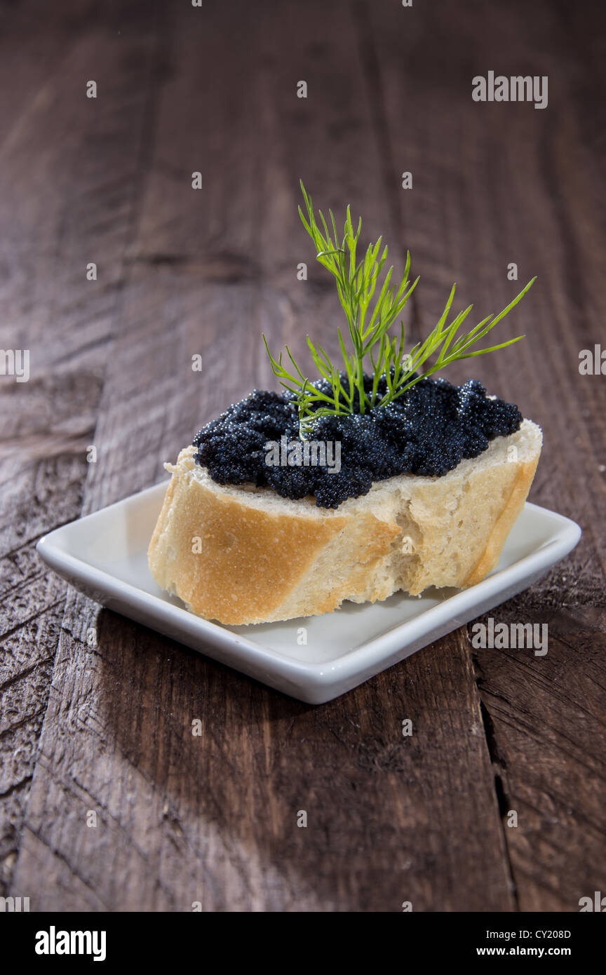 Baguette with Caviar on wooden background - Stock Image