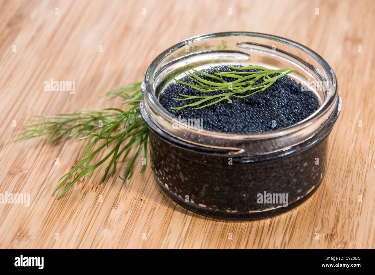 Black Caviar in a glass on wooden background - Stock Image