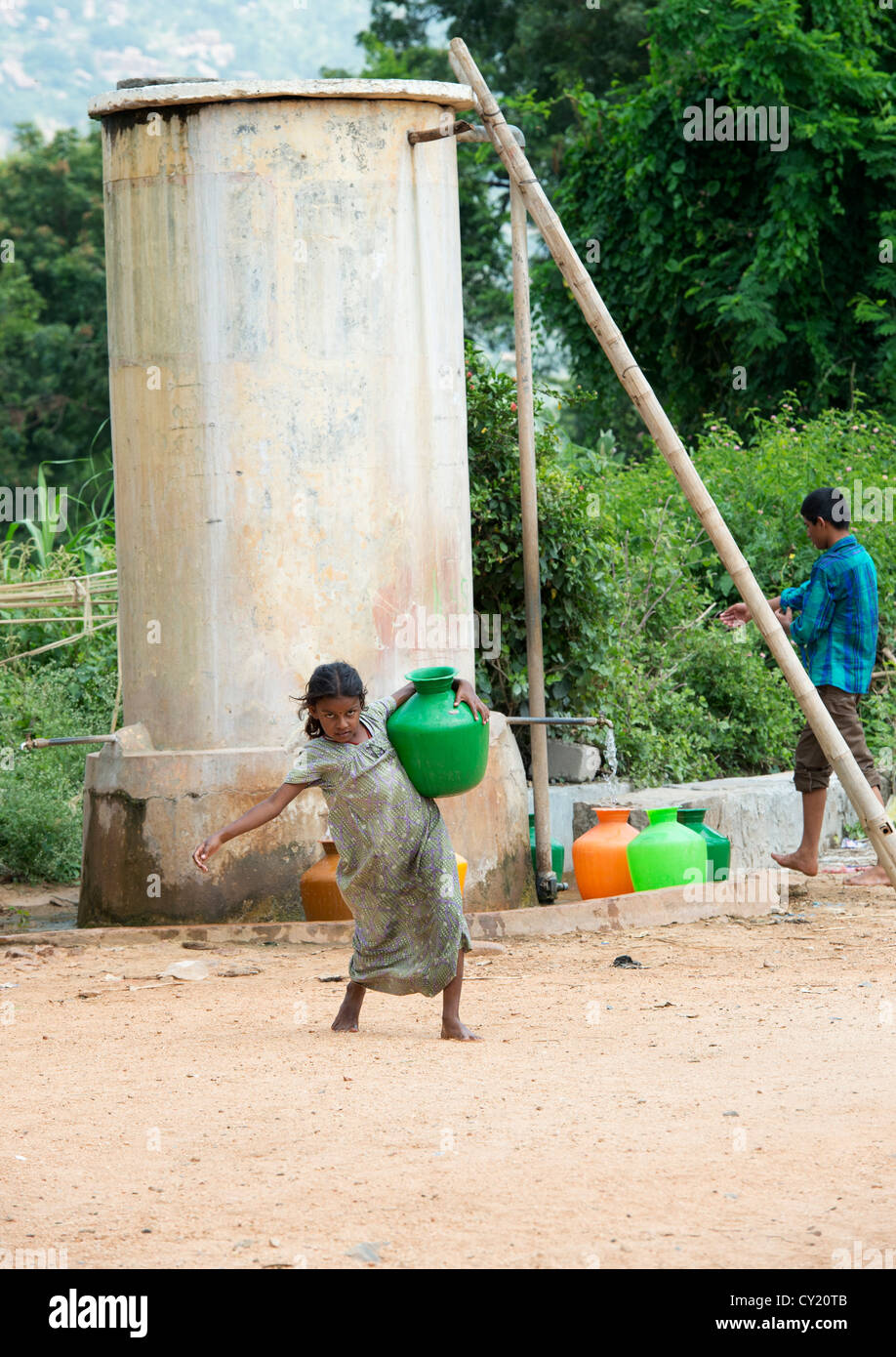 Young rural Indian village girl collecting water from a communal water tank. Andhra Pradesh, India - Stock Image