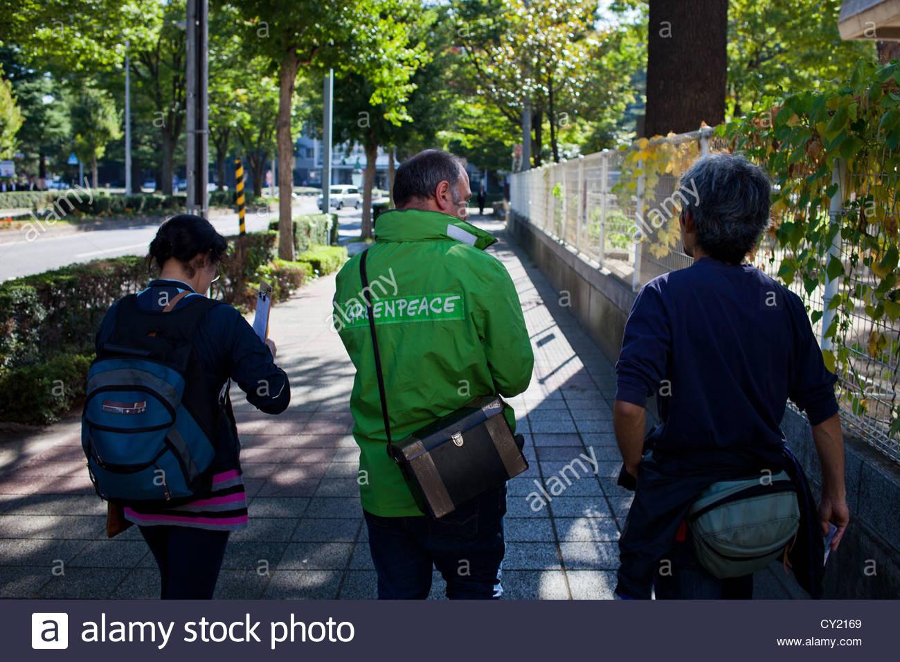 A Greenpeace radiation monitoring team checks contamination levels in Fukushima city. - Stock Image