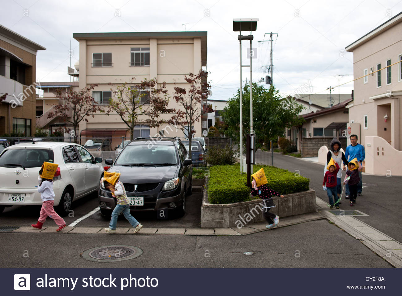 School children cross a parking lot in Watari, Fukushima city, 60km from the Fukushima Daiichi nuclear power plant. - Stock Image