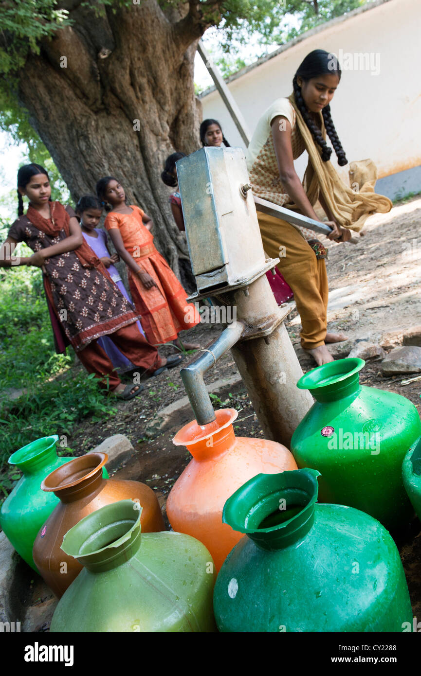 Rural Indian village girl filling water pots from a communal water pump. Andhra Pradesh, India - Stock Image