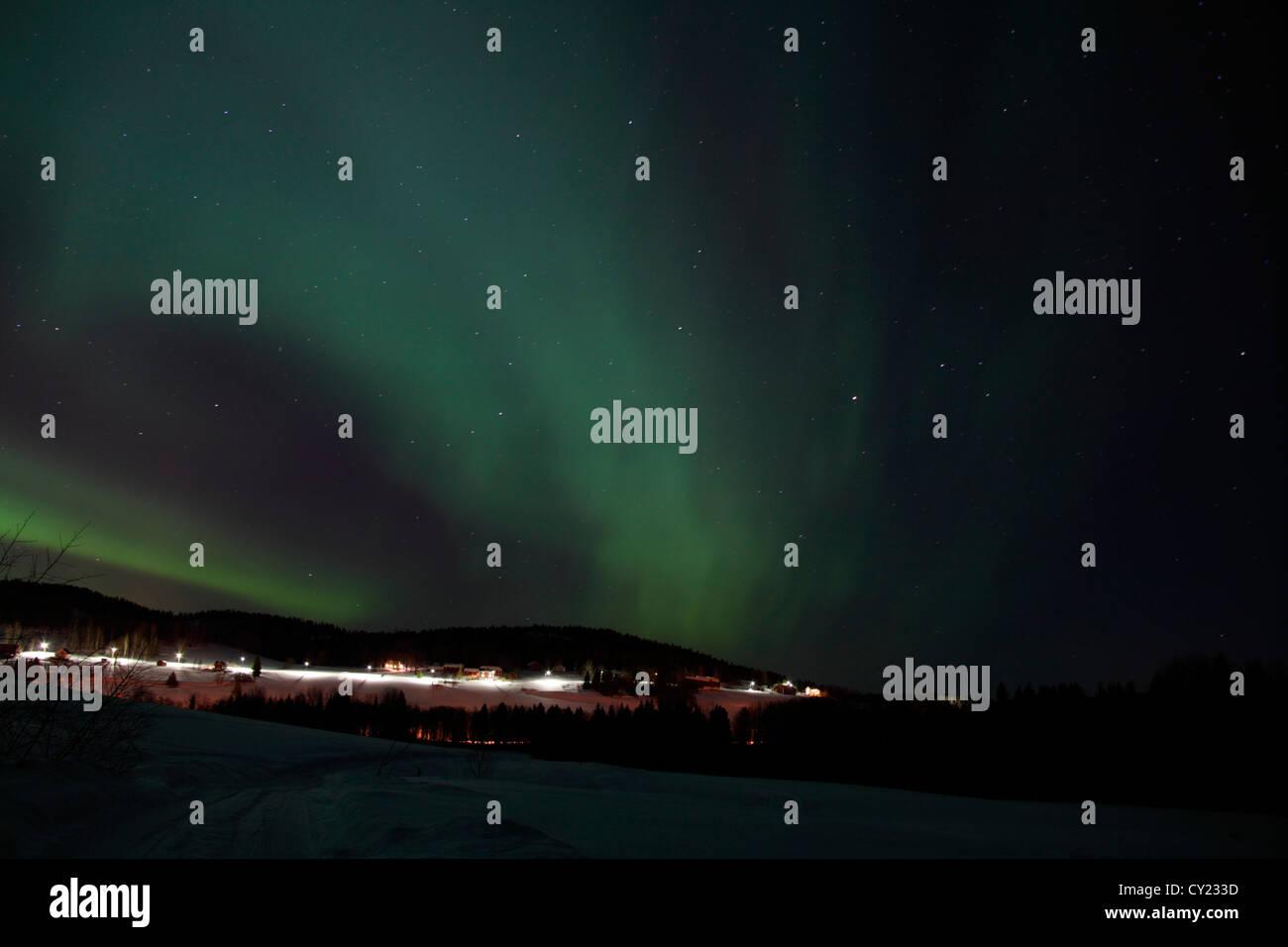 Northern lights shine over a village in northern Sweden. - Stock Image