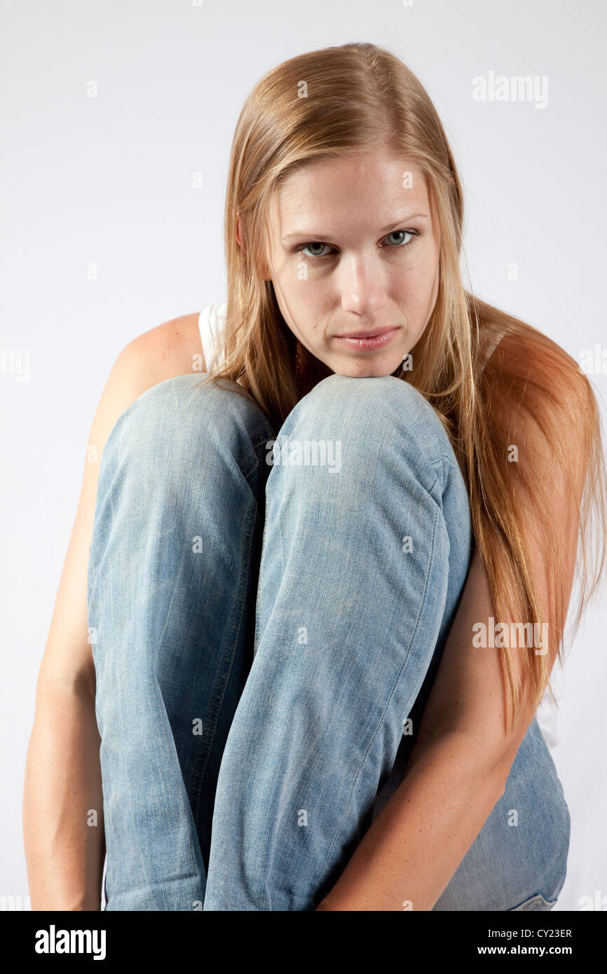 Pretty Blond Woman Sitting With Her Knee Up To Her Chest And Looking