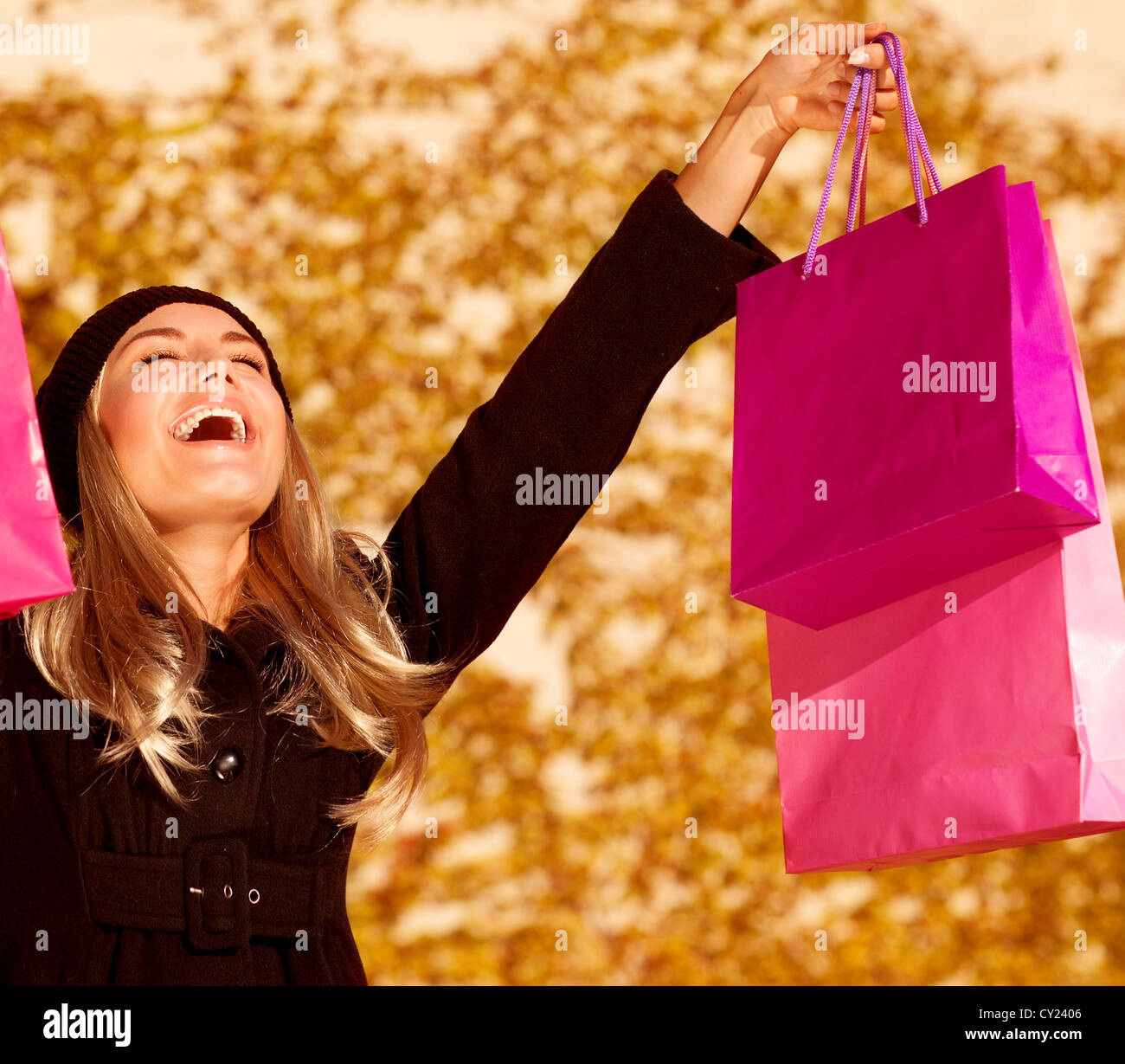 Photo of attractive woman expressing joy of her new purchase, happy good looking girl with pink shopping bags walking - Stock Image
