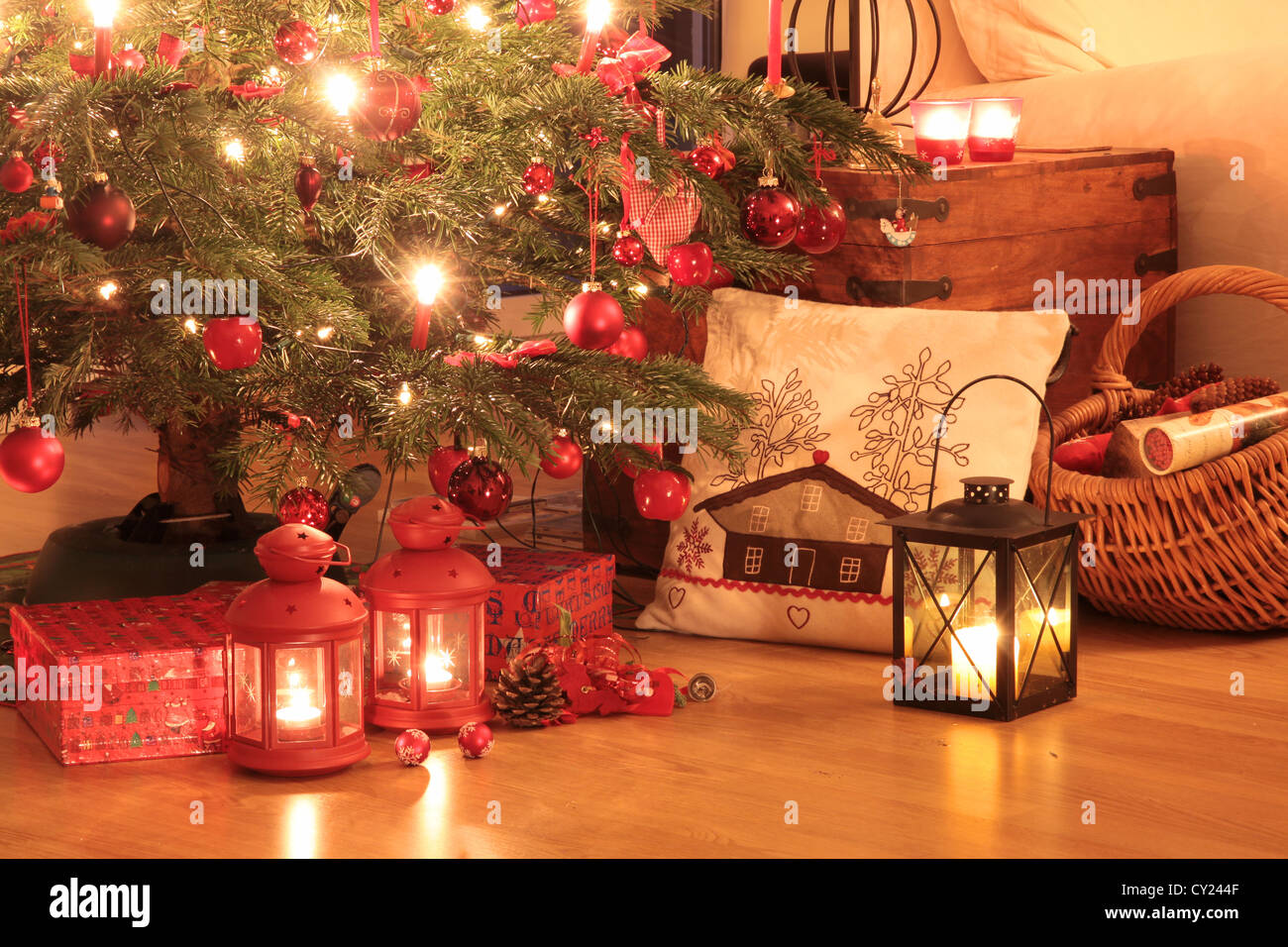 Christmas gifts in red under the Christmas tree - Stock Image