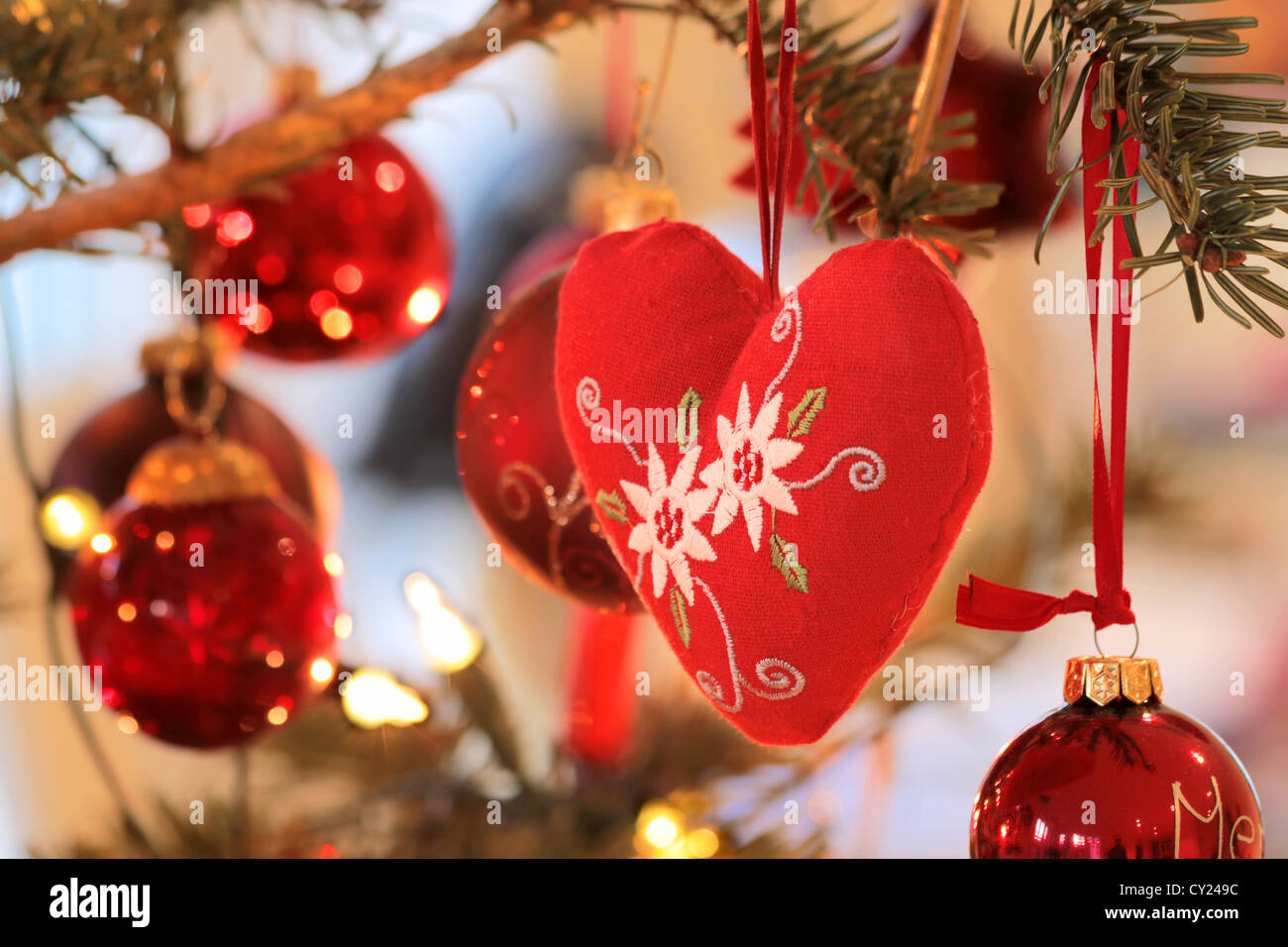 red fabric heart and red christmas balls at christmas tree stock image
